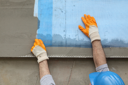 new building construction: Worker placing mesh over styrofoam insulation and mortar