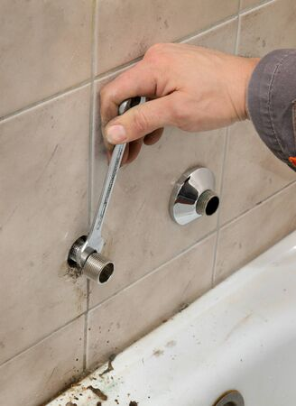 pipe fitting: Plumber fixing pipeline, pipe fitting with tool in hands