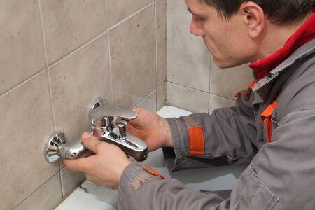 plumb: Plumber  fixing water  tap in a bathroom Stock Photo