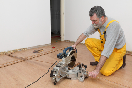 install: Worker cut wooden batten for laminate floor,  floating wood tile