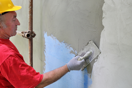 concrete structure: Worker spreading  mortar over styrofoam insulation and mesh  with trowel Stock Photo