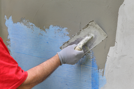 Worker spreading  mortar over styrofoam insulation and mesh  with trowel Stockfoto
