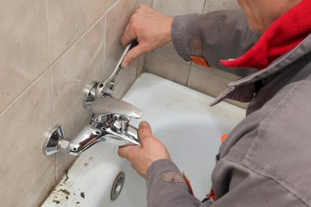 grifos: Fontanero fijación de grifo de agua en un baño usando la llave inglesa Foto de archivo