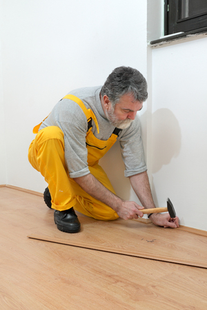 batten: Worker pound in a nail to batten for laminate floor, hammer nail,  floating wood tile