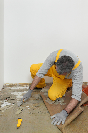 carpet clean: Worker removes glue and rubber with putty knife from floor Stock Photo