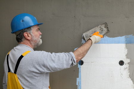 styrofoam: Worker spreading  mortar over styrofoam insulation and mesh  with trowel Stock Photo