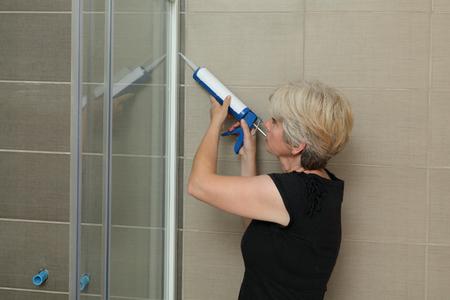 cabine de douche: Femme utilisant la cartouche de silicone pour la fixation en aluminium latte de cabine de douche Banque d'images