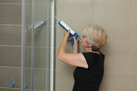 silicone: Woman using silicone cartridge for fixing aluminum batten of shower cabin Stock Photo