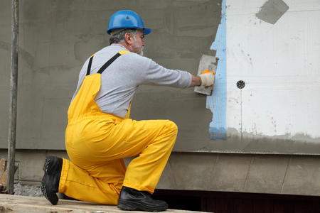 Worker spreading  mortar over styrofoam insulation and mesh  with trowel Standard-Bild
