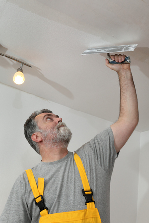 patching: Worker spreading  plaster to ceiling with trowel repairing works