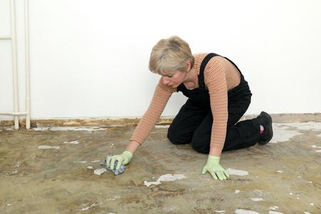 mujer arrodillada: Mujer adulta de rodillas y limpieza piso con un trapo