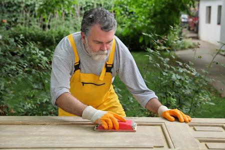 sanding block: Adult worker sanding vintage wooden door with sanding block