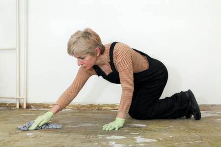 woman kneeling: Adult woman kneeling and cleaning floor with rag