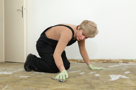 Adult woman kneeling and cleaning floor with rag