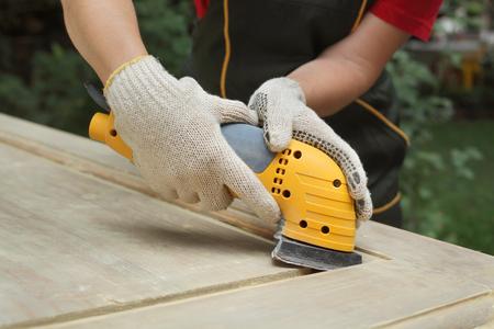 Closeup of worker hands sanding vintage wooden door with powertool