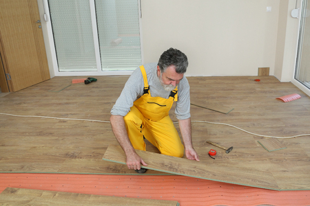 Adult male worker installing laminate floor,  floating wood tile