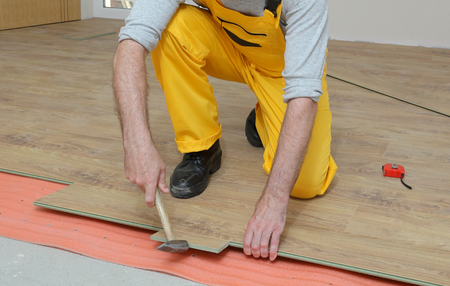 install: Adult male worker installing laminate floor,  floating wood tile