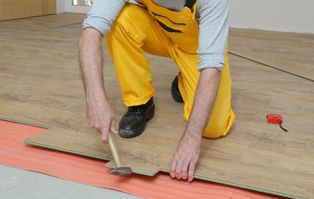 Travailleur adulte masculin installation revêtement de sol stratifié, carreaux de bois flottant