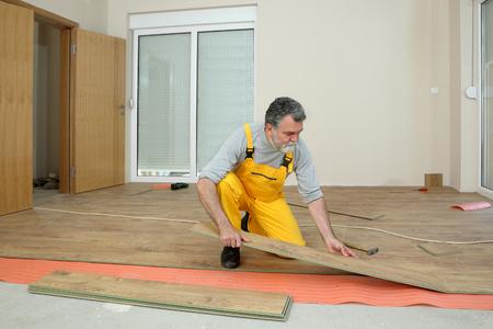 adult male: Adult male worker installing laminate floor,  floating wood tile