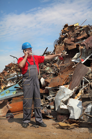 metal recycling: Metal recycling, worker gesturing and using mobile phone at junkyard Stock Photo