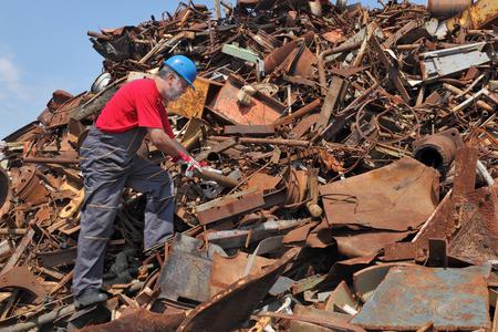 scrap heap: Worker inspecting heap of scrap metal ready for recycling
