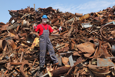 heap up: Worker gesturing at heap of scrap metal ready for recycling, thumbs up Stock Photo