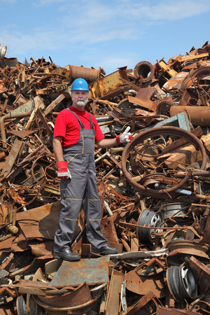 scrap: Worker gesturing at heap of scrap metal ready for recycling, thumb up