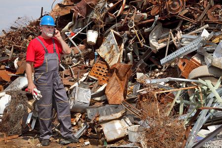 scrap heap: Metal recycling, worker speaking by mobile phone side by heap of scrap metal Stock Photo