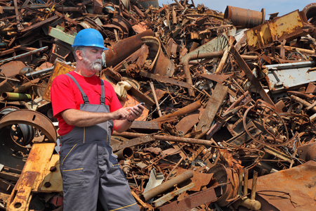destruct: Metal recycling, worker using phone to calculate price and quantity Stock Photo
