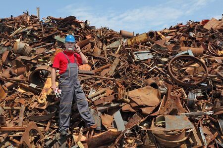 Metal recycling, worker speaking by mobile phone side by heap of scrap metal Stockfoto