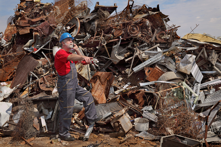 scrap: Worker gesturing at heap of scrap metal ready for recycling, pointing