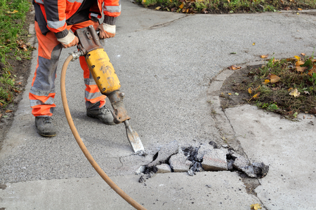 Worker at construction site demolishing asphalt with pneumatic plugger hammer Stockfoto
