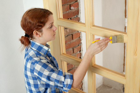 Caucasian woman: Young female worker painting new wooden door with paintbrush Stock Photo
