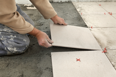 renovation: Home renovation, worker placing tiles to floor, using cement mixed with sand