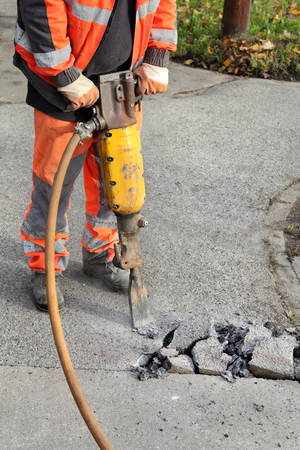 jack tar: Worker at construction site demolishing asphalt with pneumatic plugger hammer Stock Photo
