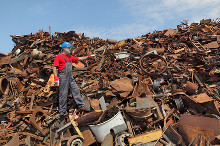 scrap iron: Worker gesturing at heap of scrap metal ready for recycling, pointing