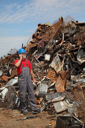 metal recycling: Metal recycling, worker speaking by mobile phone side by heap of scrap metal Stock Photo