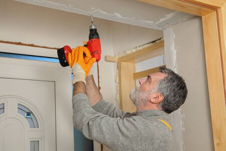 drill: Worker installing gypsum board, using electric drill or screwdriver Stock Photo