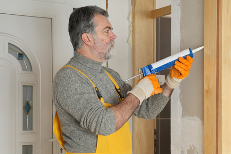 Construction worker caulking door  with silicone glue using cartridge Stockfoto