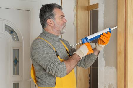 pegamento: puerta de calafateo trabajador de la construcción con pegamento de silicona con el cartucho Foto de archivo