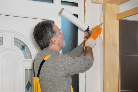 polyurethane: Worker install wooden door, using polyurethane foam to fix it at wall Stock Photo