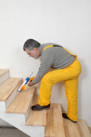 caulking: Construction worker caulking wooden stairs with silicone glue using cartridge