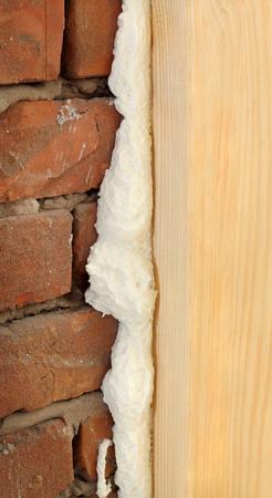 pu foam: Wooden door or window install, closeup of polyurethane foam wood and bricks Stock Photo