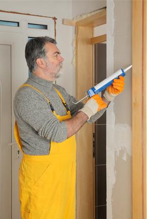 caulk: Construction worker caulking door  with silicone glue using cartridge tool
