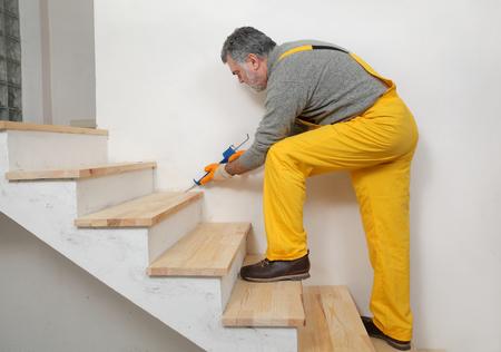 Trabajador de la construcción de calafateo escaleras de madera con pegamento de silicona utilizando cartucho, rehabilitación de viviendas