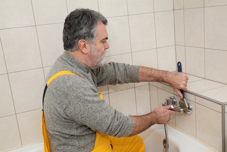 pipe wrench: Mid adult plumber fixing water  tap at bath tube in a bathroom