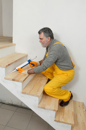 Construction worker caulking wooden stairs with silicone glue using cartridge, home renovation Stockfoto