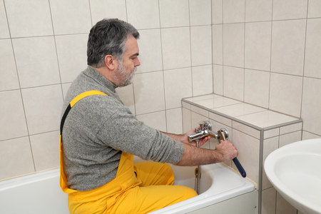 mid adult: Mid adult plumber fixing water  tap at bath tube in a bathroom
