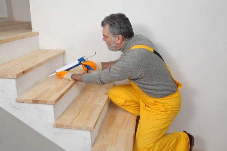 caulking: Construction worker caulking wooden stairs with silicone glue using cartridge, home renovation Stock Photo
