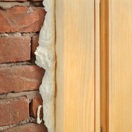 Holztür oder ein Fenster installieren, Nahaufnahme von Polyurethanschaum Holz und Ziegel